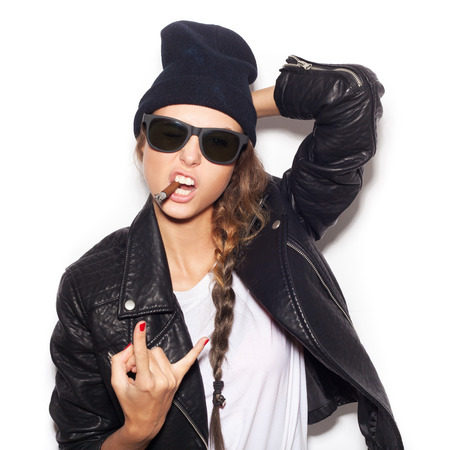 ciggy: Hipster girl in sunglasses and black beanie smoking and giving the Rock and Roll sign. Stock Photo