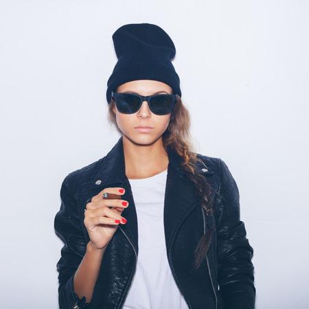 chica fumando: Chica inconformista en gafas de sol y de cuero negro chaqueta de fumar cigarros.