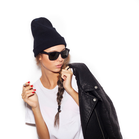 Hipster girl in sunglasses and black leather jacket smoking cigarette.  White background, not isolated photo