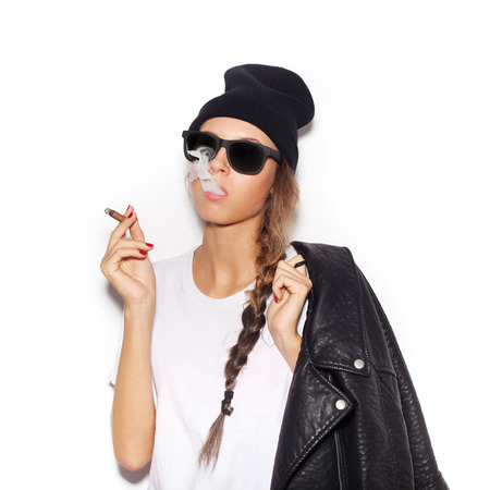 Hipster girl in sunglasses with black leather jacket smoke tobacco.   photo