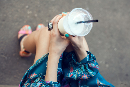 Girl with glasses drinking milkshake. Outdoor lifestyle portrait of woman Standard-Bild