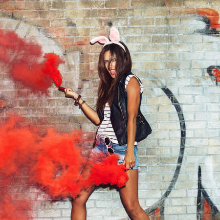 sexy shorts: Naughty hipster girl in pink rabbit ears dancing with red smoke bombs. Outdoors lifestyle portrait Stock Photo