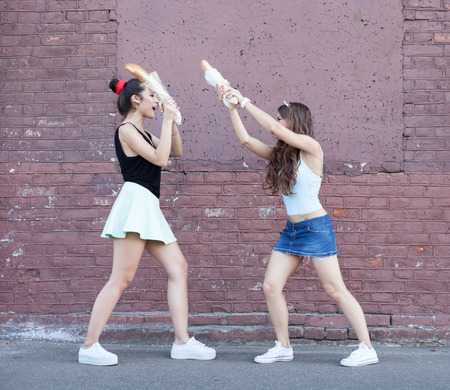 women fighting: Two women fighting bread. Outdoor lifestyle portrait