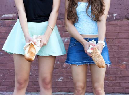 pene: Due giovani donne divertirsi con il pane. Outdoor ritratto stile di vita