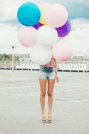 colores pastel: Mujer joven feliz de pie detr�s de grandes globos de l�tex de colores. Aire libre, estilo de vida