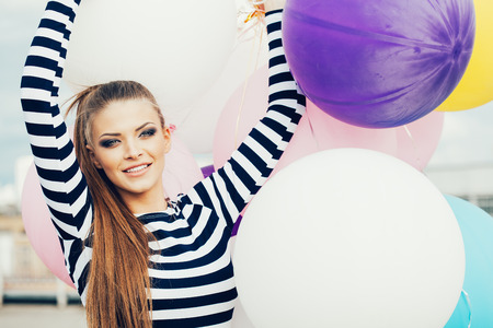 Happy young woman with colorful latex balloons, outdoor photo
