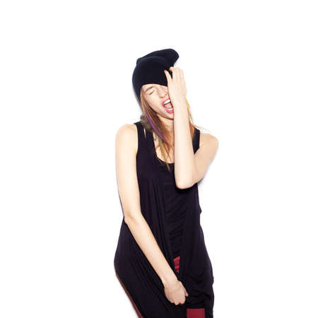 young woman in black beanie . Beautiful Girl opening Mouth. Emotion.  Hairstyle. Makeup.  White background, not isolated photo