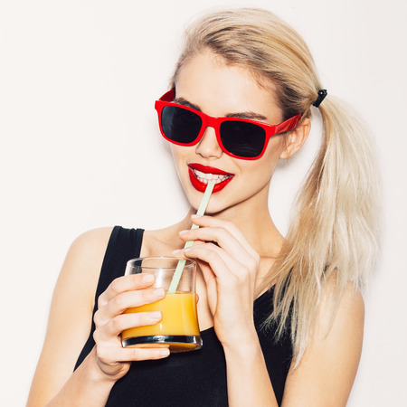 drinking alcohol: Summer closeup portrait of pretty smiling blonde woman in sunglasses with cocktail