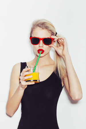 Portrait of pretty smiling blonde woman in sunglasses with cocktail
