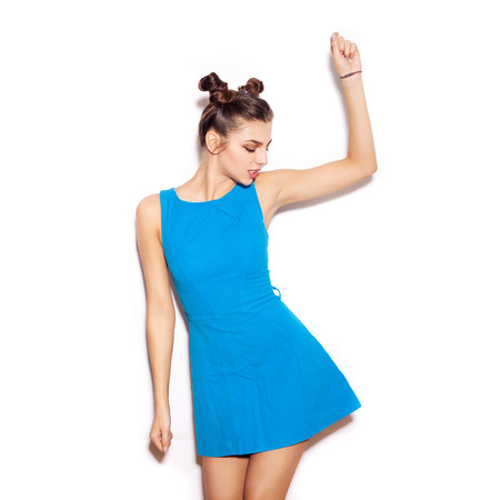 promotion girl: Happy young woman dancing. Beauty girl with bright makeup hairstyle with horns in a blue dress having fun. On a white background, not isolated