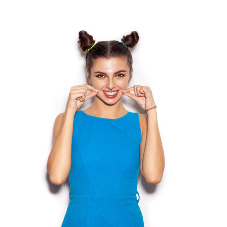 Young woman laughing and showing smile by fingers. Beauty girl with bright makeup hairstyle with horns in a blue dress having fun. On a white background, not isolated