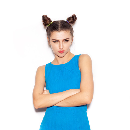 Woman with serious face looking at the camera. Beauty girl with bright makeup hairstyle with horns in a blue dress having fun. On a white background, not isolated