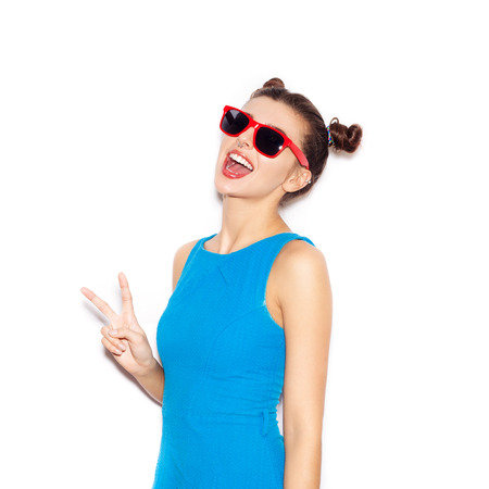Young woman in sunglasses  laughing. Beauty girl with bright makeup hairstyle with horns in a blue dress having fun. On a white background, not isolated