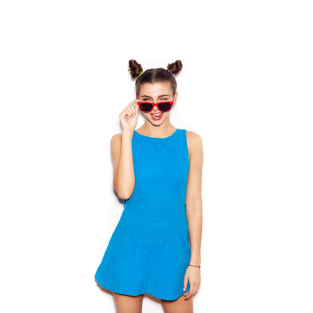Brunette Woman in sunglasses showing tongue. Beauty girl with bright makeup hairstyle with horns in a blue dress having fun. On a white background, not isolated