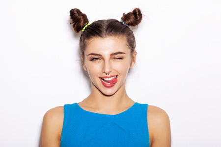 Young happy woman winking and showing tongue. Beauty girl with bright makeup hairstyle with horns in a blue dress having fun. On a white background, not isolated