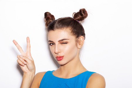 Young woman saluting and winking. Beauty girl with bright makeup hairstyle with horns in a blue dress having fun. On a white background, not isolated Standard-Bild