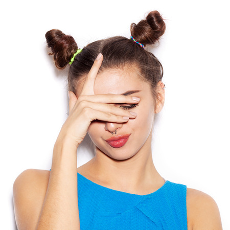 mouth to mouth: Close-up of young woman  showing emotions. Beauty girl with bright makeup hairstyle with horns in a blue dress having fun. On a white background, not isolated Stock Photo