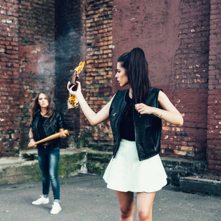 rout: Two Bad girls with Molotov cocktail bomb in the street.  Outdoor lifestyle portrait