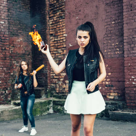 rout: Two Bad fan girls with Molotov cocktail bomb in the street.  Outdoor lifestyle portrait