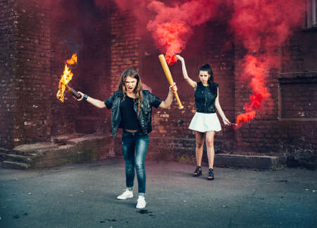 molotov: Two women protesters with Molotov cocktail bomb in the street.  Outdoor lifestyle portrait