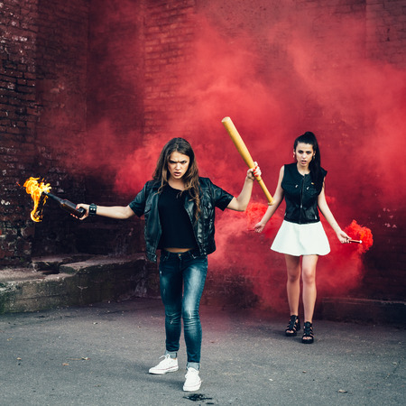 rout: Two Bad fan girls with Molotov cocktail and red smoke bomb in the street.  Outdoor lifestyle portrait