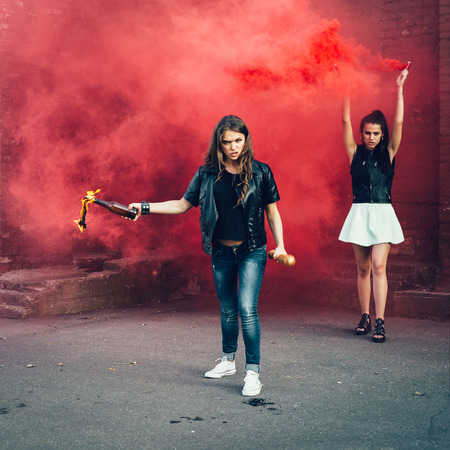 molotov: Two Bad fan girls with Molotov cocktail bomb in the street.  Outdoor lifestyle portrait