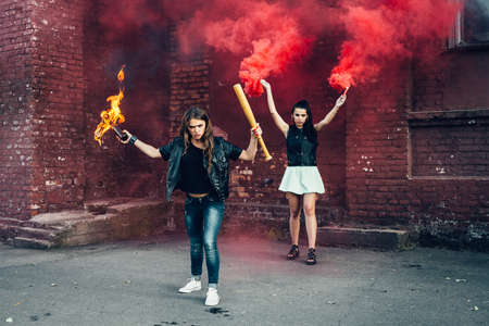 rout: Two aggressive women with Molotov cocktail and red smoke bomb in the street.  Outdoor lifestyle portrait