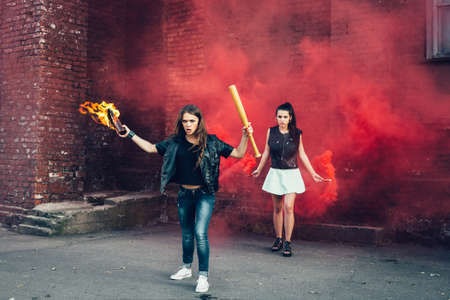 molotov: Two young fans with Molotov cocktail and red smoke bombin the street.  Outdoor lifestyle portrait