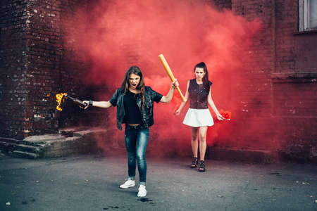 molotov: Two Bad girls with Molotov cocktail and red smoke bomb in the street.  Outdoor lifestyle portrait