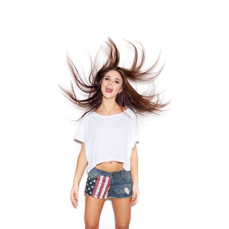 Beautiful girl shaking her hair . White background, not isolated photo