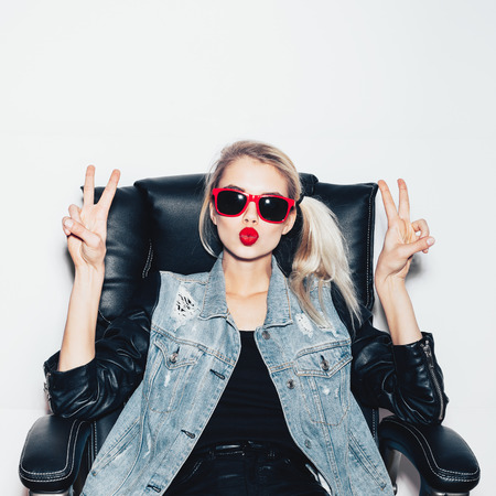 Young blonde woman in sunglasses sit on black office chair and showing victory by finger. Fashion hipster girl.  White background, not isolated