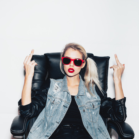 Young blonde woman in sunglasses sit on black office chair and showing middle finger . Fashion hipster girl.  White background, not isolated