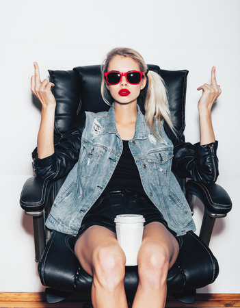 Young blonde woman in sunglasses sit on black office chair and showing middle finger and holding a cup of coffee knees . Fashoin hipster girl.  White background, not isolated photo