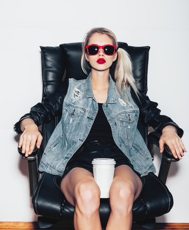 Sexy  blonde woman in sunglasses sit on black office chair and holding a cup of coffee knees. Fashion hipster girl. White background, not isolated Stock Photo
