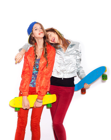 skaters: Two girl skaters go crazy and have fun together.  Beautiful sporty women Emotion.  White background, not isolated Stock Photo