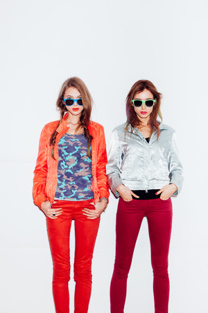 Two young sporty girl friends in sunglasses standing together.  indoor portrait. White background not isolated photo