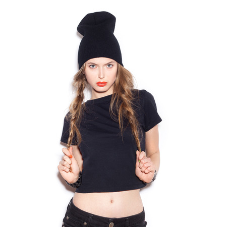 Fashion girl hipster hold by hands her two long braids. Woman in black clothes. White background, not isolated