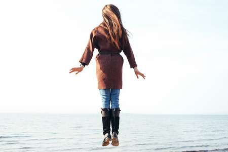 hovering: Beautiful young woman in a coat hovering over the sea on a sunny day. Outdoor lifestyle portrait Stock Photo