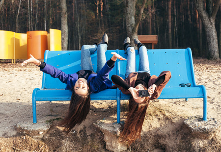 fun: Two funky friends having fun and taking photos lying upside down on a bench on the beach. Outdoor lifestyle portrait
