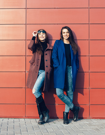 Two pretty women  in a coats posing near red wall on a sunny day. Outdoor lifestyle portrait Standard-Bild