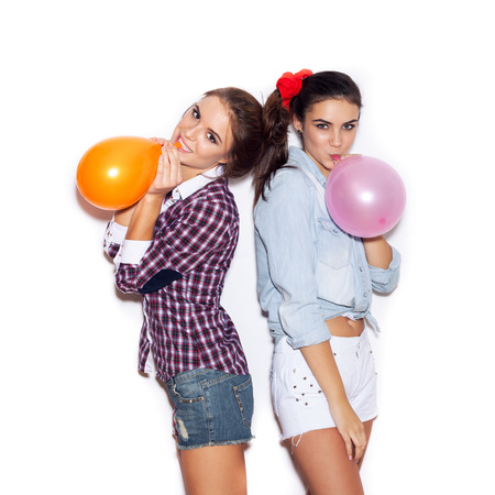 to inflate: Two girlfriends inflate colored balloons. White background not isolated