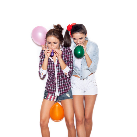 inflate: Two pretty young women inflate colored balloons. White background not isolated