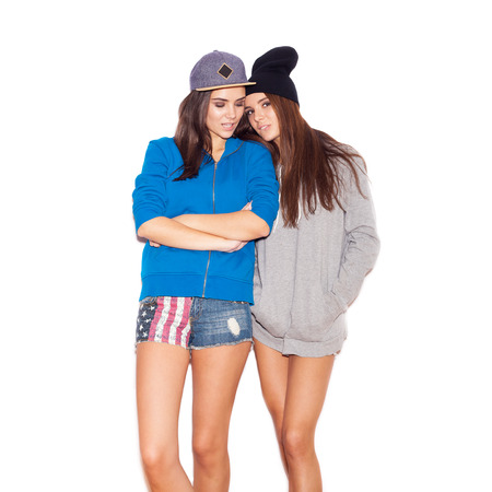 Two lovely young girl friends standing together.  indoor portrait. White background not isolated photo