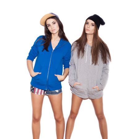 Two young stylish girlfriends in hoodies standing together.  indoor portrait. White background not isolated photo