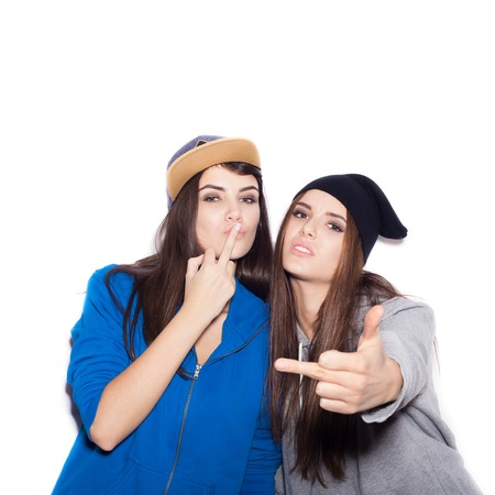 naughty woman: Swag girls showing middle finger. Fashion hipster women. White background not isolated