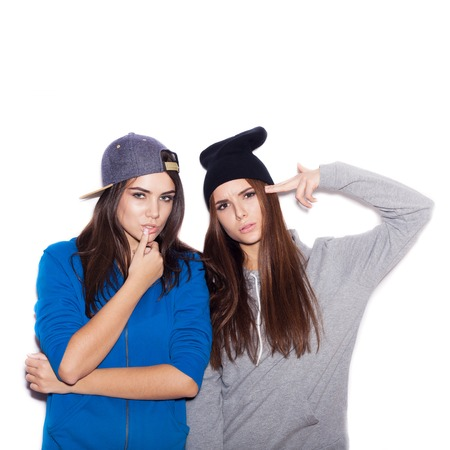 Close-up of young women showing emotions.  Swag girls standing together on white background not isolated photo