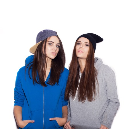 Two arrogant swag girlfriends standing together on white background not isolated photo
