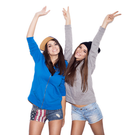 Two young stylish girlfriends in hoodies having fun together.  indoor portrait. White background not isolated photo