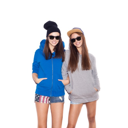 Young blonde women in sunglasses smiling. Two Fashion hipster girls.  White background, not isolated