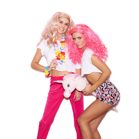 Two pretty girs in colorful wigs and clothing have fun with a unicorn on white background not isolated photo